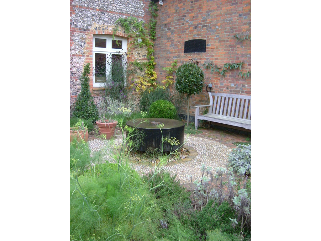 Herb garden and water feature designed by Acres Wild, landscaped by The Garden Company