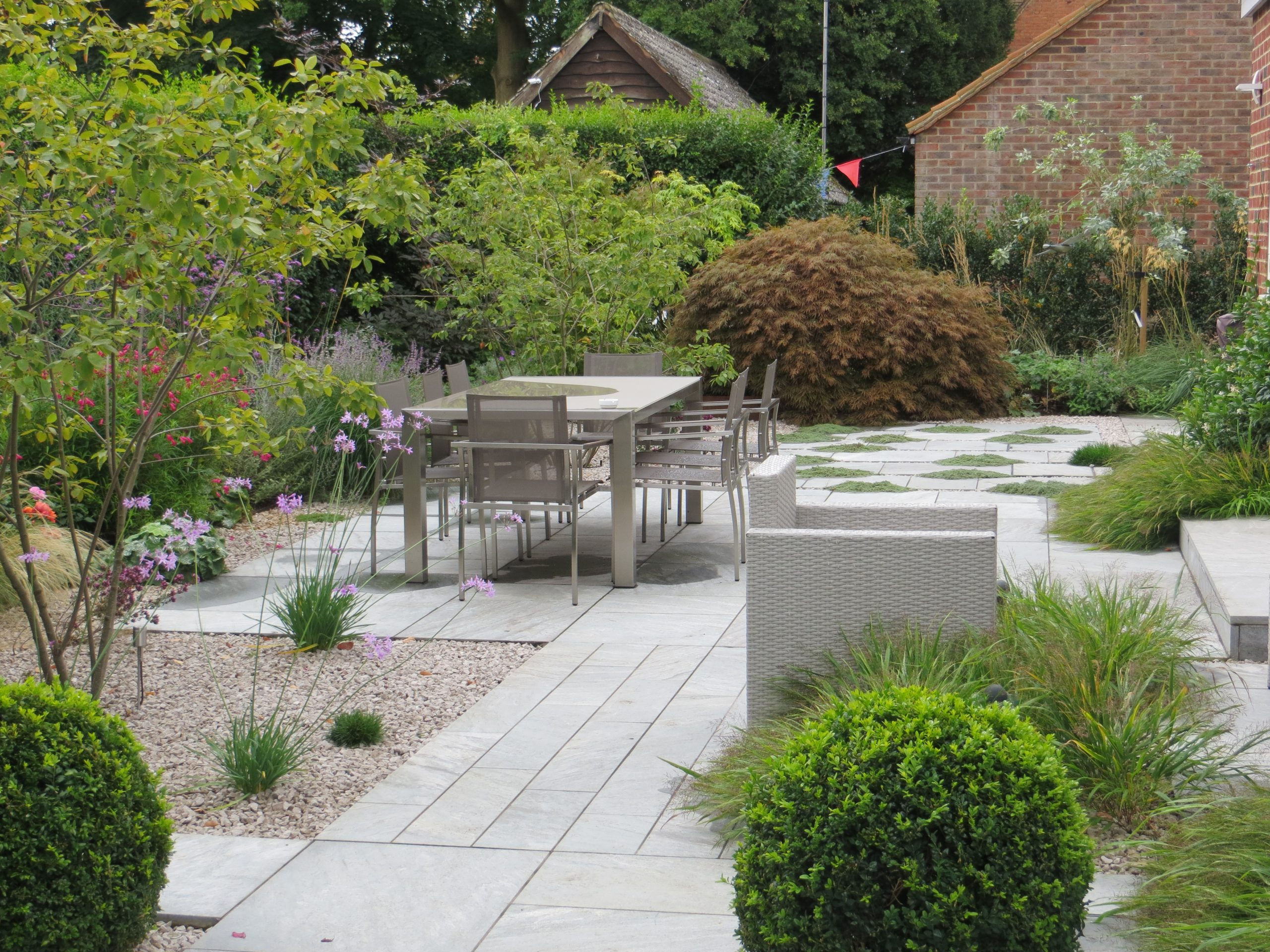 Shows outdoor dining area with table and chairs