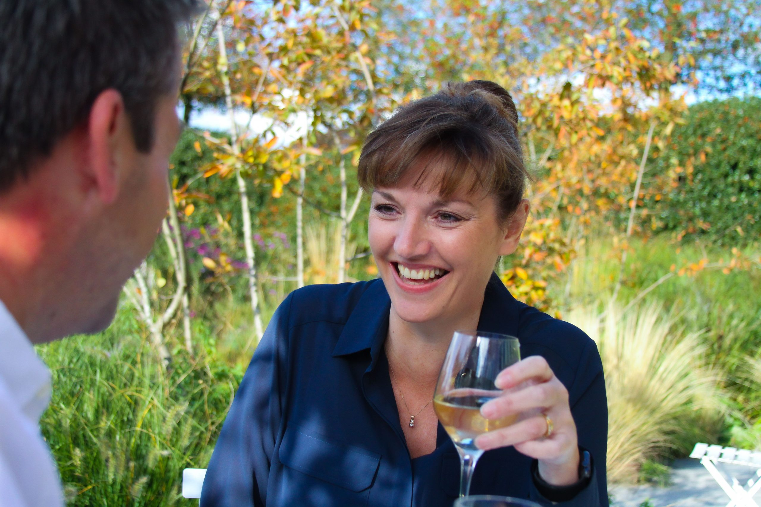 Shows woman enjoying a drink and relaxing in the garden